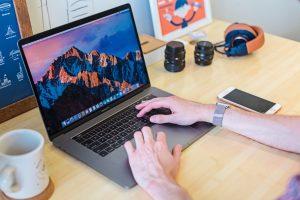 MacBook Pro turned on beside white ceramic mug